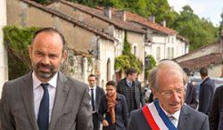 Le premier ministre entamant une visite du village accompagné du maire